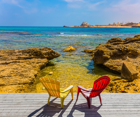 Ruins of the ancient port of Caesarea. Red and yellow plastic armchairs stand on the shore of the Mediterranean Sea. Spring day in Israel. Concept of archeological and historical tourism