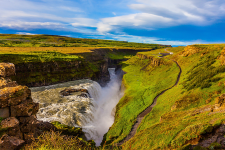 Sunny summer day. Huge masses of water crash down into a narrow gorge. The most picturesque waterfall in Iceland - Gullfoss. The concept of extreme and phototourism Stok Fotoğraf - 123585181