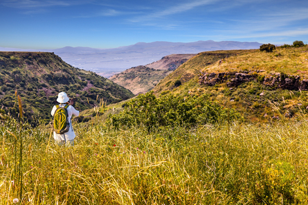 Woman with backpack in white hat photographs picturesque landscape. Jewish Easter in Israel.  Spring blooming Golan Heights - a mountain plateau of volcanic origin. The concept of ecological, active and photo tourism Stock Photo