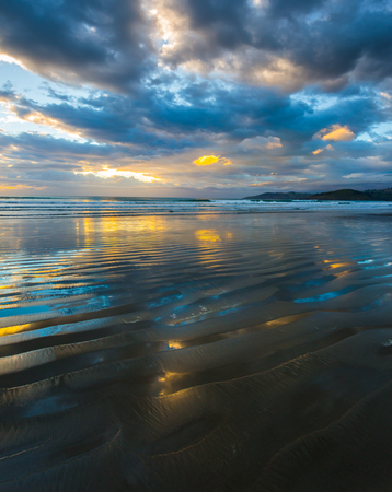 Sunrise over the ocean. Gentle cloud colors are reflected in the ocean water. Light wind causes small ripples in the water. The art of artistic photography. New Zealand, Pacific Coast. The concept of artistic photography