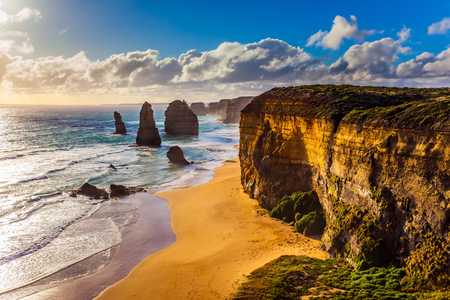 Powerful Pacific surf breaks down on the shore. Grandiose coast of Australia. Rocks of the Twelve Apostles at sunset. The concept of exotic, active and photo-tourism Stock Photo