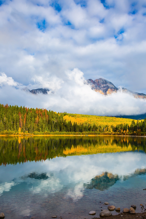 Patricia Lake amongst the forests, yellow bushes and mountains. Autumn in the Rocky Mountains of Canada Stock Photo