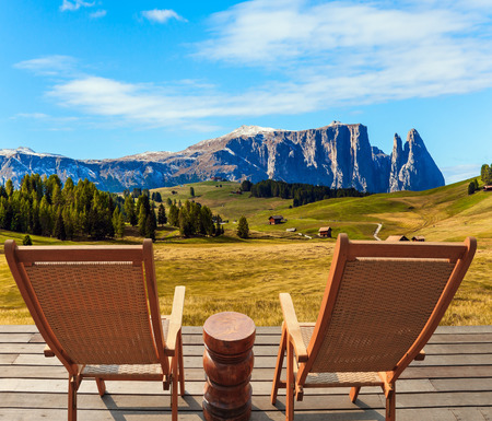 Two comfortable lounge chairs on the hotel terrace. Alpe di Siusi is charming plateau in the Dolomites. Wonderful holiday in the fresh air. The concept of walking, ecological and photo tourism Banco de Imagens