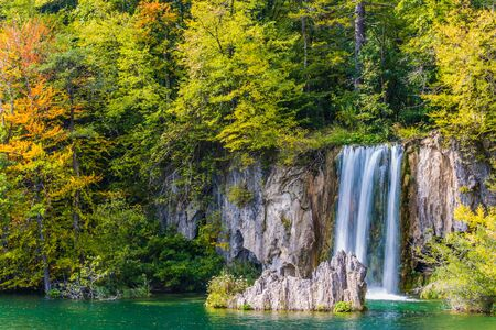 Lovely waterfall falls from a vertical ledge. Travel to the fabulous country of the Plitvice Lakes. The concept of ecological, active and phototourism Imagens