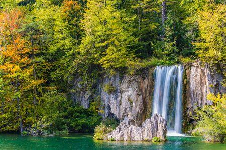 Mooie waterval valt van een verticale richel. Reis naar het fantastische land van de Plitvicemeren. Het concept van ecologisch, actief en fototoerisme Stockfoto