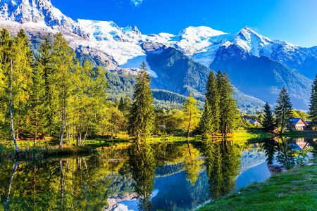 City Park is illuminated by the sunset. The lake reflected the evergreen spruce and snow-capped Alps. Concept of active and ecological tourism. The mountain resort of Chamonix, Haute-Savoie