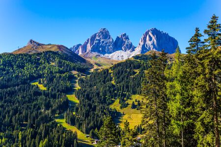 The coniferous forests at the foot of limestone and dolomite rocks. The picturesque route in the Italian Dolomites, the Southern Limestone Alps. The concept of active and car tourism