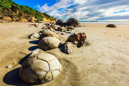 Series of mysterious round boulders Moeraki and their shattered remnants on a sandy beach.  New Zealand. Low tide in the Pacific. Popular tourist attraction.The concept of exotic and ecological tourism