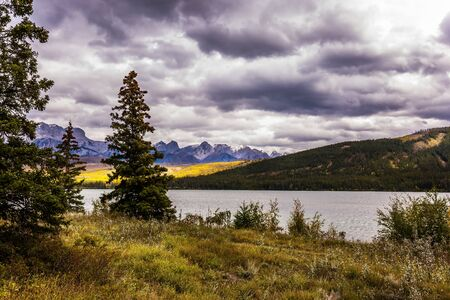 Heavy clouds looming over the valley along the Pocahontas road. Rocky Mountains of Canada. Autumn wind drives ripples in the dark water. Concept of active and photo-tourism