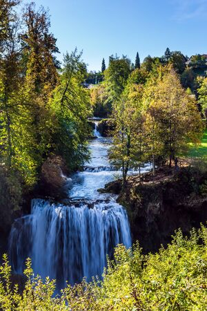 Magnificent cascade of waterfalls on the Korana River. Magnificent dense forests surround the city and the river. The small Croatian town of Slunj. The concept of ecological, active and photo tourism