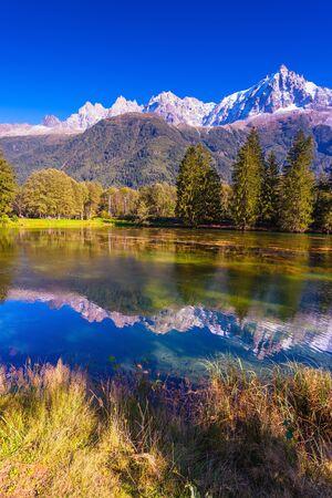Park Miejski rozświetla zachodzące słońce. Górski kurort Chamonix w Górnej Sabaudii. Jezioro odbijało ośnieżone Alpy
