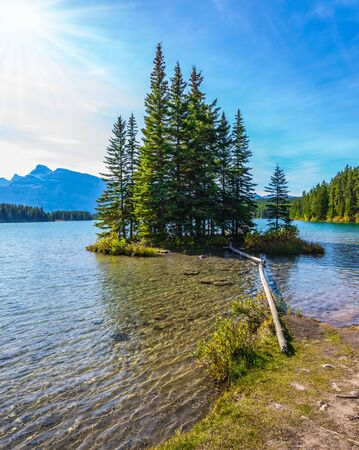 The morning sun warms the picturesque lake and a small island. Golden Autumn in Canada. Lake Two Jack in the Rocky Mountains. The concept of ecological and active tourism