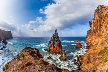 The blinding midday sun illuminates the rocky shore. The boiling turquoise surf, sharp red rocks. Madeira is a magical island in the Atlantic. The concept of active, ecological and photo tourism