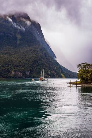 Cold wind from Antarctica ruffles the water of the Milford Sound fjord. New Zealand - land of goblins and hobbits. Concept of exotic, active and photographic tourism Фото со стока - 129019534