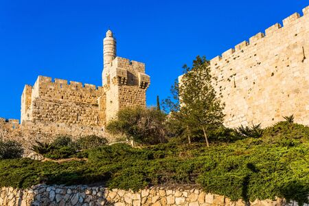 Hot summer sunset. Monumental walls of Jerusalem. The height of the walls is 12 meters. Ancient Citadel - Tower of David. The concept of historical, religious, pilgrim and photo tourism 免版税图像