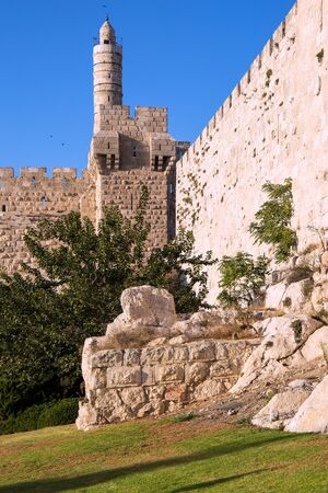 Hot summer sunset. The fortress wall of old Jerusalem. Adorable green lawn growing under ancient walls. Ancient Citadel - Tower of David. The concept of historical, pilgrim and photo tourism