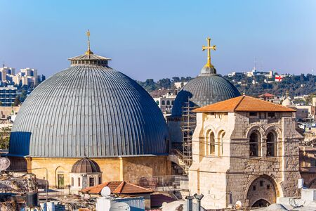 The roofs of Jerusalem. Domes of the Temple of the Holy Sepulcher. Golden crosses sparkle in the sunset. Bird's eye view. The concept of historical, religious, pilgrim and photo tourism