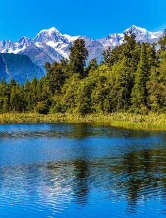 Lake Matheson is glacial lake. South Island of New Zealand. Water reflects Mount Cook and Mount Tasman. Mountain peaks covered with snow. The concept of ecological, active and photo tourism