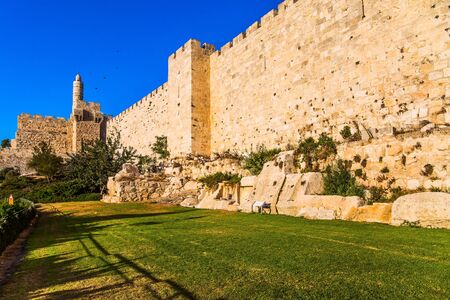 Ancient Citadel - Tower of David. Hot summer sunset. Fortress wall of old jerusalem. The height of the walls is 12 meters. The concept of historical, religious and photo tourism