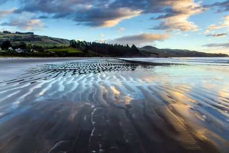 Gentle cloud colors are reflected in the ocean water. Low tide. Strips of sand and water left by the ocean tide. The art of artistic photography. New Zealand, Pacific Coast The concept of ecological and photo tourism