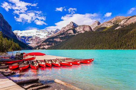 Red canoes for tourists are moored to the coast. Glacial Lake Louise in Canadian Rockies. The lake is surrounded by high mountains and coniferous forests. The concept of ecological and photo tourism