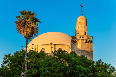 Muslim mosque and crescent minaret on the dome. Sunset. The muslim mosque and crescent minaret  is lit by the setting sun. Israel. The concept of religious, historical and photo tourism