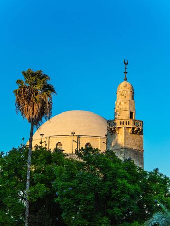 Muslim mosque and crescent minaret on the dome. Summer sunset. The mosque and crescent minaret is lit by the setting sun. Israel. The concept of religious, historical and photo tourism