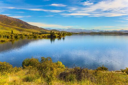 Magic South Island, New Zealand. The picturesque lake Dunstan near the town of Cromwell. Emerald-colored deep lake water and grassy lawns. The concept of ecological and photo tourism 版權商用圖片