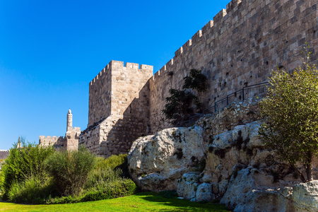 Hot summer sunset. The fortress wall of old Jerusalem. Ancient Citadel - Tower of David. Adorable green lawn growing under ancient walls. The concept of historical, pilgrim and photo tourism Editorial