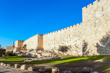 Summer sunset. The fortress wall of ancient Jerusalem. Old Citadel - Tower of David. Adorable green lawn growing under ancient walls. The concept of historical, pilgrim and photo tourism Editorial