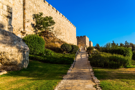 Stone-paved footpath through green grass lawn. The fortress wall of old Jerusalem. Hot summer sunset. The concept of historical, pilgrim and photo tourism Editorial
