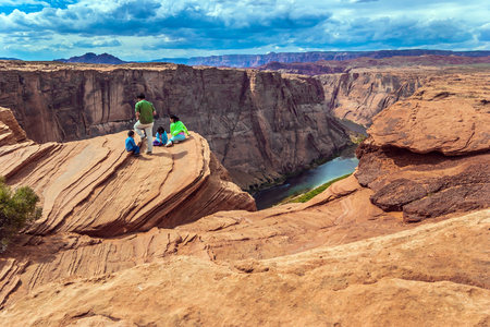 ARIZONA, USA - OCTOBER 8, 2005: Tourists watch the beautiful scenery. Scenic Horseshoe-shaped bend of the Colorado River. Arizona. The concept of active and photo tourism