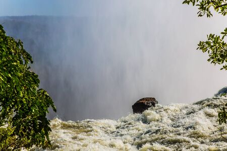 Grand Victoria Falls. Giant cloud of mist rose above the waterfall. Fantastic walk after the rainy season. Victoria is a waterfall on the Zambezi River. Concept of active, extreme and photo tourism