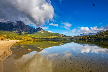 Pyramid Mountain and magnificent cumulus clouds reflected in the smooth water of Pyramid Lake. Morning in the Rocky Mountains, Canada