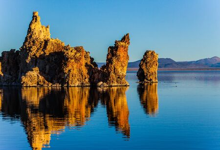Picturesque Mono lake. Sunset. The columns-remains of bizzare shapes of Tufa are  reflected in the water of the lake. Birds on the lake. The concept of ecological, exotic and photo tourism