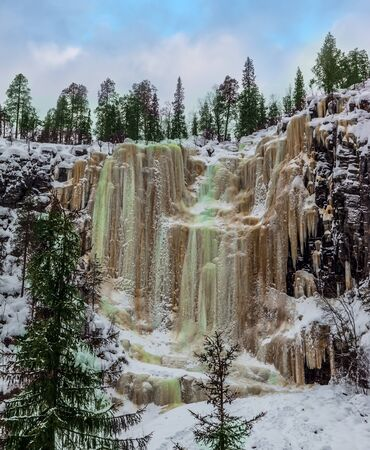 Wall of frozen water. Multicolored icicles of a frozen waterfall picturesquely fall off a steep cliff.   Christmas in Lapland. The concept of photo and eco-tourism