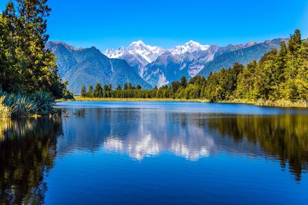 Magnificent snow-capped mountains surround the smooth, cold waters of Lake Matheson. The forests and  Mount Cook and Mount Tasman. The concept of ecological, active and photo tourism 免版税图像