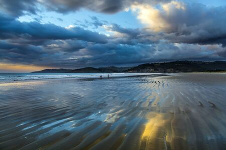 Sunrise over the ocean. Low tide. Strips of sand and water left by the ocean tide. New Zealand, Pacific Coast. The concept of artistic photography