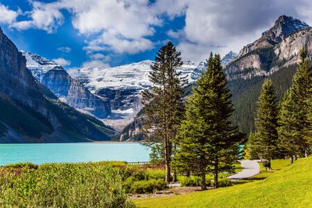 Glacial Lake Louise. Sunny day. Travel to the Rocky Mountains of Canada. The lake with azure water is surrounded by mountains and forests. The concept of ecological, active and photo tourism