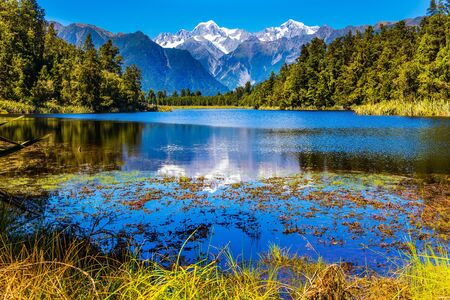 Mirror glacial Lake Matheson surrounded by mountains Mount Cook and Mount Tasman and forests. Mountain peaks covered with snow. The concept of ecological, active and photo tourism