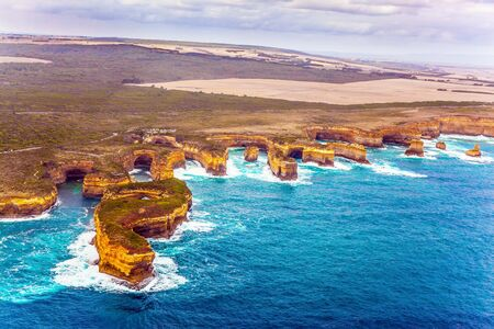 Australia, Port Campbell Park. Great Ocean Road and coastal cliffs of the Twelve Apostles is a group of limestone cliffs. The concept of extreme, active and photo tourism. Picture taken from a helicopter