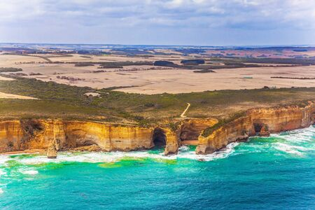Scenic coastline. Picture taken from a helicopter. Great Ocean Road and the Twelve Apostles - a group of sandstone cliffs on the Pacific coast. Australia. The concept of extreme, active and photo tourism