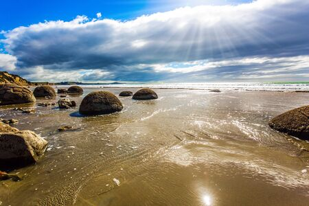 The South Island of New Zealand. Popular tourist attraction. Moeraki Boulders is the group of large spherical boulders. Low tide in the Pacific ocean. The concept of exotic and ecological tourism