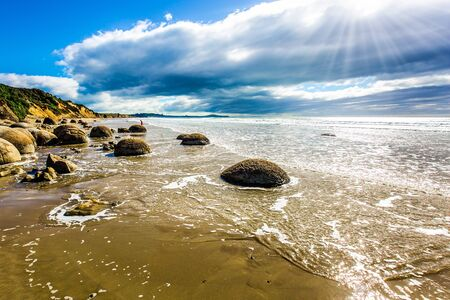 Moeraki Boulders is the group of large spherical boulders. The South Island of New Zealand. Popular tourist attraction. Low tide in the Pacific ocean. The concept of exotic and ecological tourism