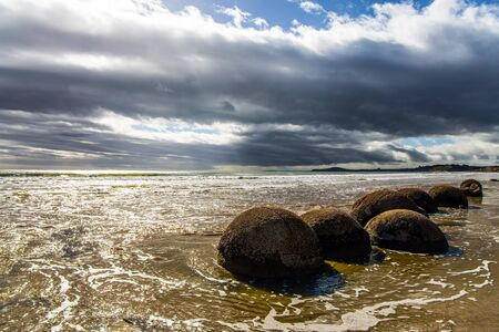 The Pacific ocean tide begins. Moeraki boulders - group of large round boulders. New Zealand. The sun's rays are reflected in the ocean water. The concept of ecological, exotic and phototourism
