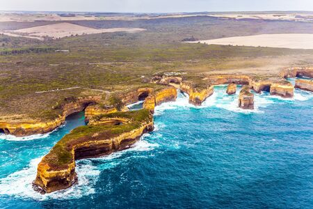 Scenic coastline. Picture taken from a helicopter. Australia, Port Campbell Park. Great Ocean Road and the Twelve Apostles is a group of limestone cliffs. The concept of extreme, active and photo tourism