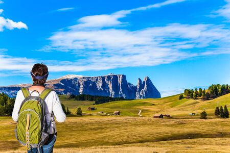 Alpe di Siusi is charming plateau in the Dolomites, Italy. Slender woman with a green backpack admires the beautiful scenery. Indian summer in the Dolomites. The concept of walking, ecological and photo tourism Banco de Imagens