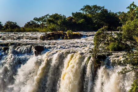 Grand Victoria Falls. Victoria is a waterfall on the Zambezi River in South Africa. Thundering Smoke National Park in Zambia. The border of Zambia and Zimbabwe. Fantastic walk in the high season after rain. Concept of active, extreme and photo tourism.