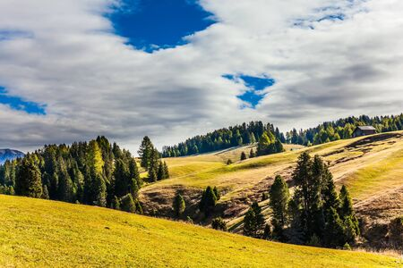 Powerful ridge of rocks on the horizon. Val Gardena, Italy. Alpe di Siusi is charming plateau in the Dolomites. The concept of walking, ecological and photo tourism Banco de Imagens