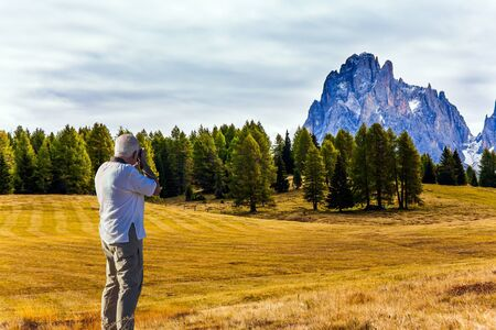 Gray-haired tourist photographs a picturesque landscape. Indian summer in the Dolomites. Alpe di Siusi is charming plateau in the Dolomites, Italy. The concept of walking, ecological and photo tourism